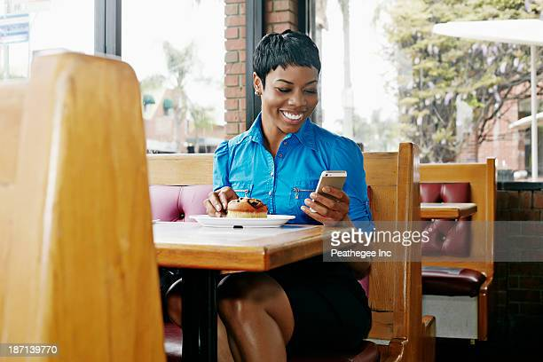 African American businesswoman using cell phone in restaurant