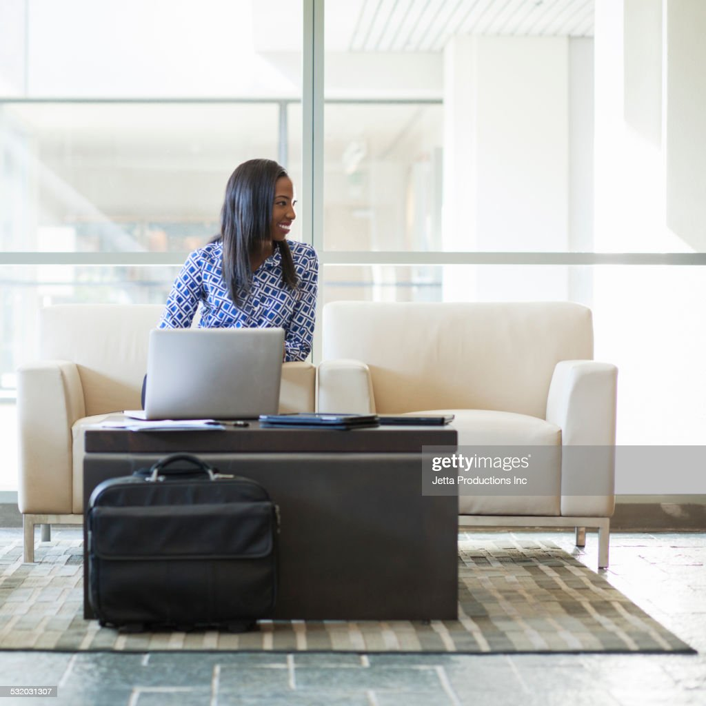 African American businesswoman using laptop in office lobby : Stock Photo