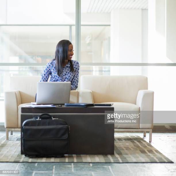 African American businesswoman using laptop in office lobby