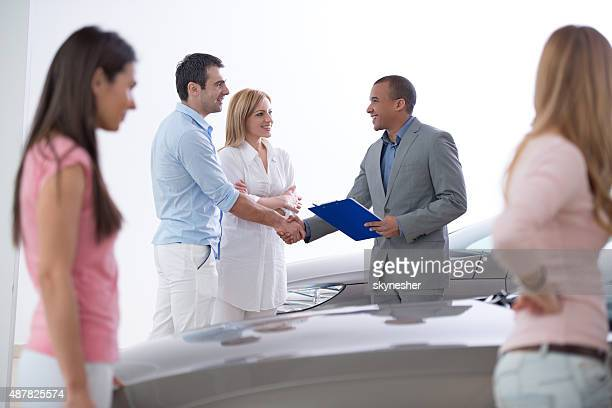 African American car sales person shaking hands with costumer.
