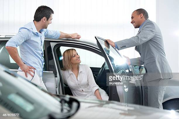 African American car salesperson talking with his customers.