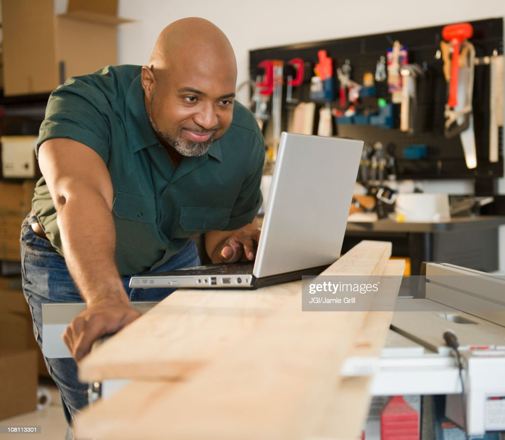 African American carpenter using laptop in workshop : Stock Photo