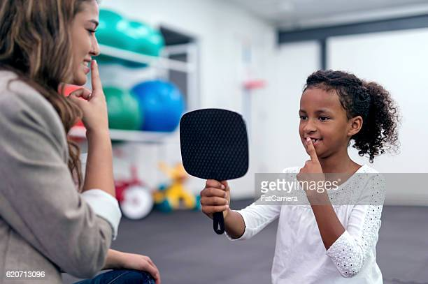 African American child holding mirror and touching lips for therapy