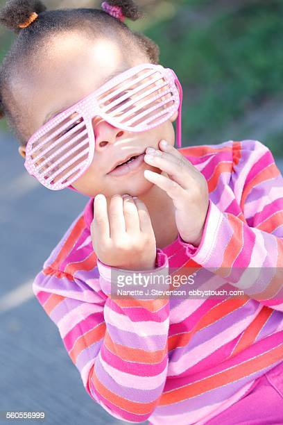 african american child wearing pink sunglasses - nanette j stevenson stock photos and pictures