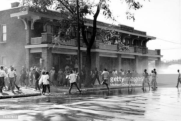 African American children are attacked by dogs and water cannons during a protest against segregation organized by Reverend Dr Martin Luther King Jr...