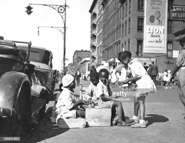 African American children at play on Lenox Avenue in Harlem New York New York 1950
