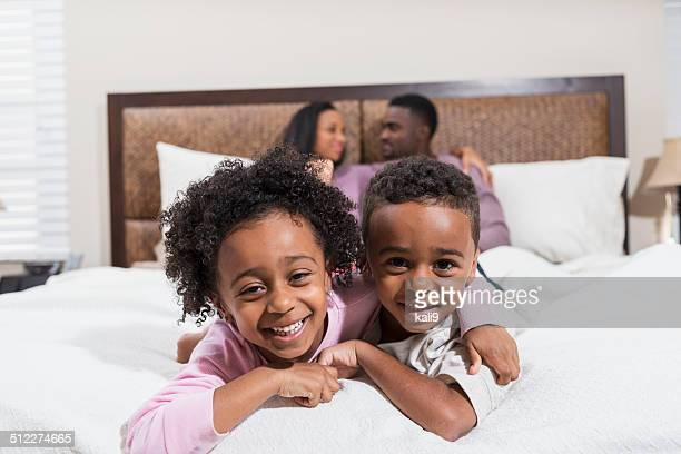 African American children in pajamas on bed, parents in background