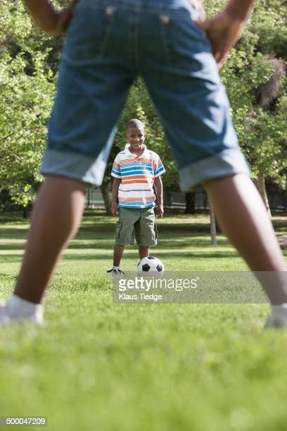 African American children playing soccer in park
