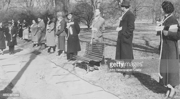 African American citizens stand in a park with nooses around their necks to protest lynchings Monroe Georgia 1946