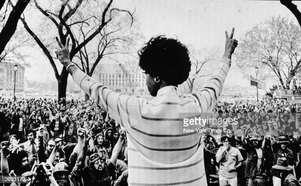 African American congresswoman Shirley Chisholm gives the peace sign to a crowd of protestors as she speaks to veterans on the Washington Mall...
