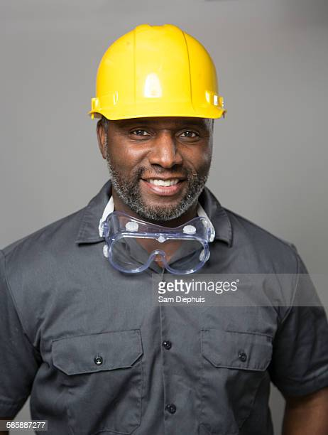 African American construction worker wearing hard hat and goggles