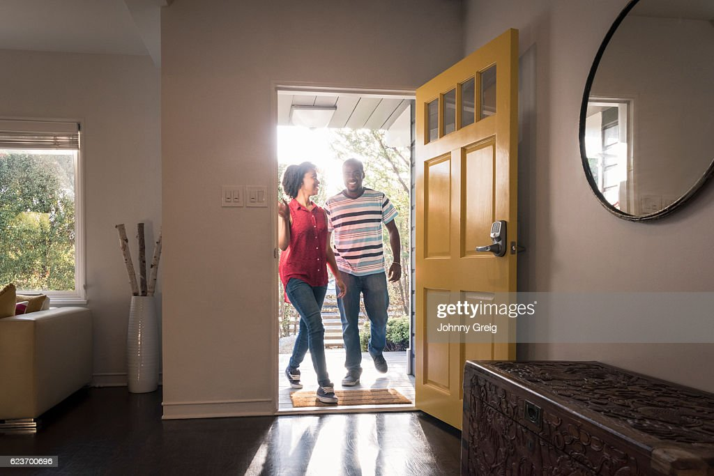 African American couple arriving home in doorway, smiling : Stock Photo