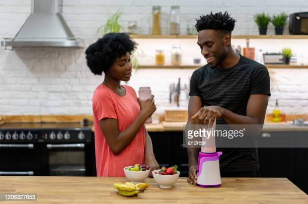 african american couple at home making healthy smoothies - healthy eating stock pictures, royalty-free photos & images