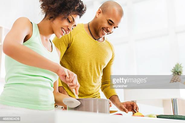 African American couple cooking in the kitchen.