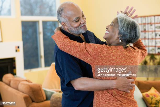 African American couple dancing in living room