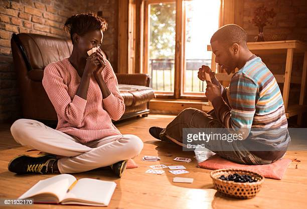 african american couple having fun while playing cards at home. - poker card game stock photos and pictures