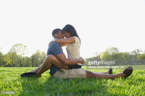 African American couple hugging in park