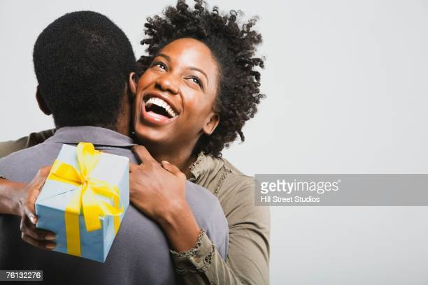 African American couple hugging with gift