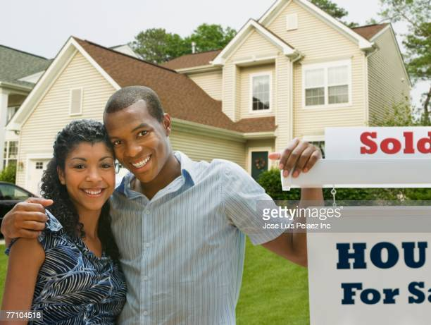 African American couple in front of new house