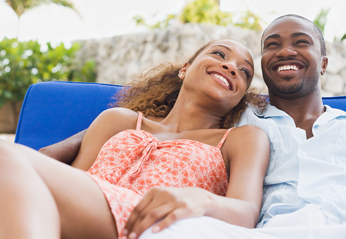 African American couple laying on lounge chair - gettyimageskorea