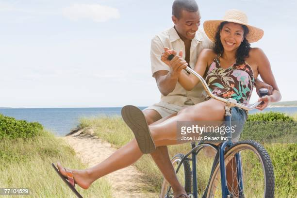 african american couple on bicycle at beach - black shorts stock pictures, royalty-free photos & images