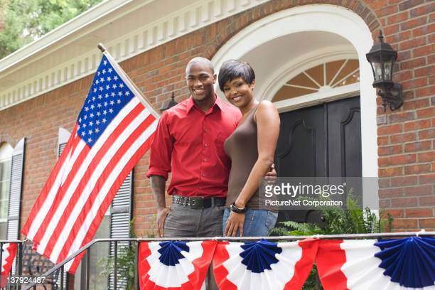 African American couple on front stoop decorated for Fourth of July