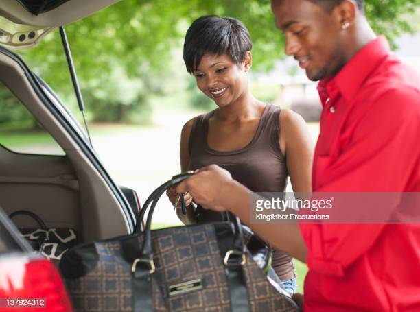 African American couple packing for car trip