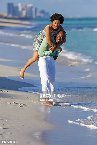 African American couple playing on beach