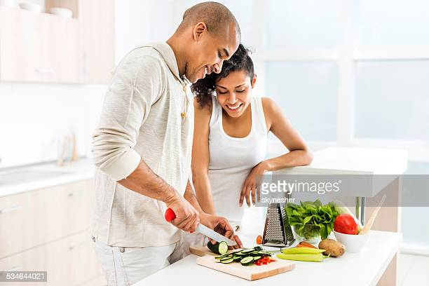 African American couple preparing salad.