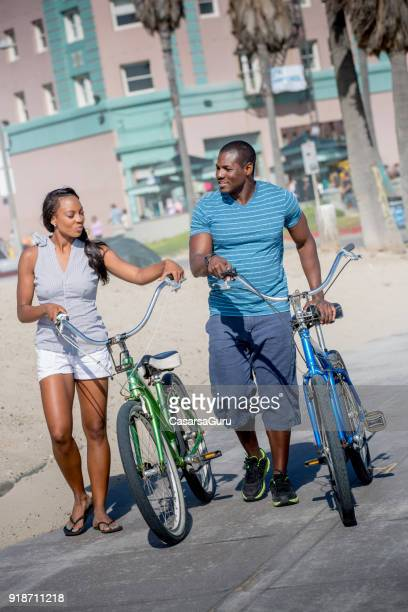 African American Couple Pushing Bikes on Pavement Path