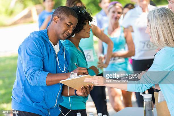 african american couple registering for marathon or 5k race - charity benefit stock pictures, royalty-free photos & images