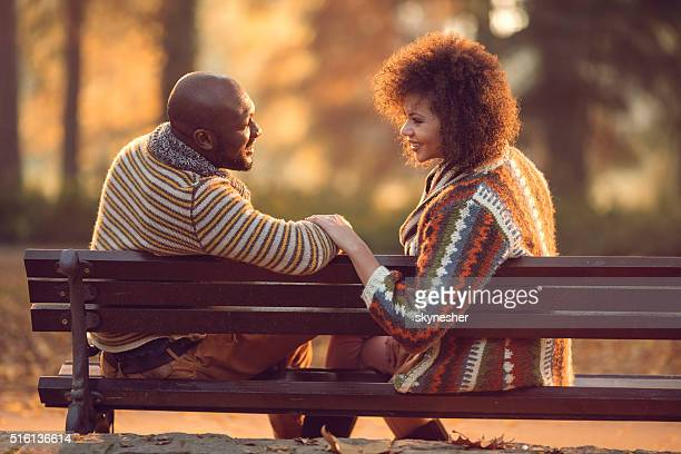 African American couple relaxing on bench and communicating in nature.