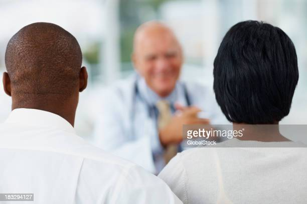 African American couple sitting in front of a doctor