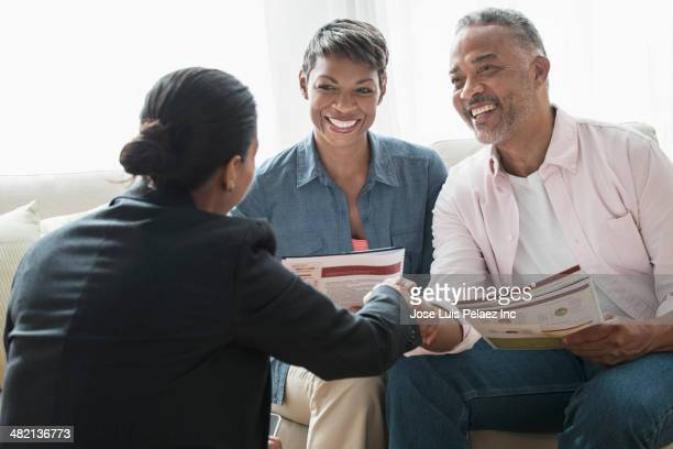 african american couple talking to businesswoman - financial advisor stock pictures, royalty-free photos & images