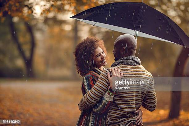African American couple under umbrella during rainy autumn day.