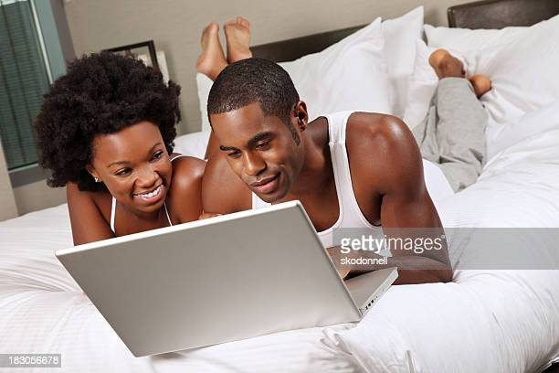 African American Couple Using a Laptop on the Bed