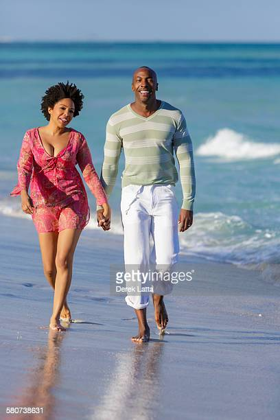 African American couple walking on beach