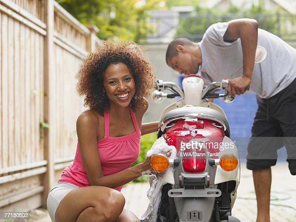 African American couple washing motor scooter