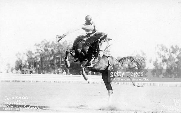 African American cowboy Jess Stahl smiles as he rides horse Glass Eye in the area at the California Rodeo Salinas as spectators watch in the distant...