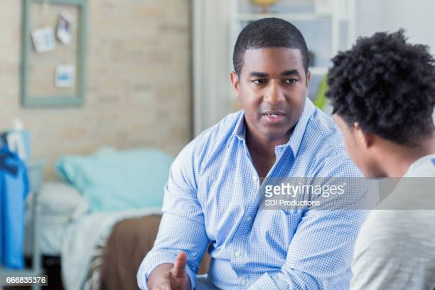 African American dad has serious conversation with his son