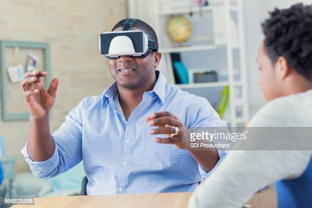 African American dad uses virtual reality goggles