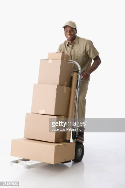 African American delivery man pushing hand truck