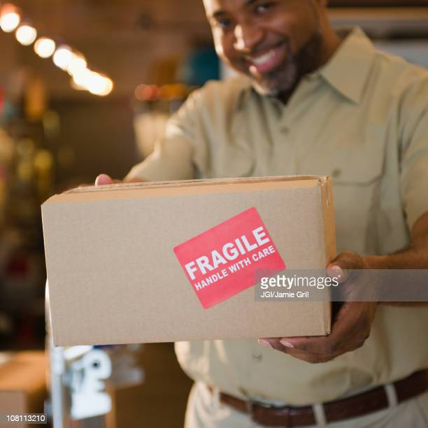 African American deliveryman holding out box with 'fragile' sticker