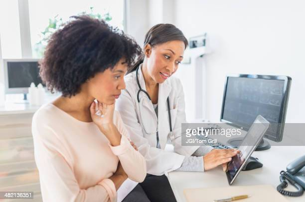 african american doctor and patient talking in office - doctor's surgery stock pictures, royalty-free photos & images