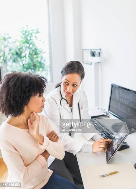 African American doctor and patient talking in office
