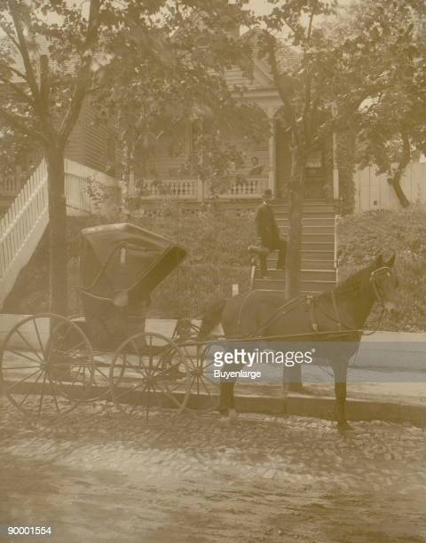 African American doctor carrying small leather bag standing on steps to residence horsedrawn carriage in the foreground