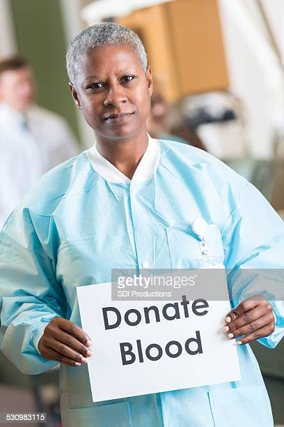 African American doctor holding donate blood sign in donation lab