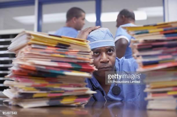 african american doctor looking at stacks of charts - overwerkt stockfoto's en -beelden