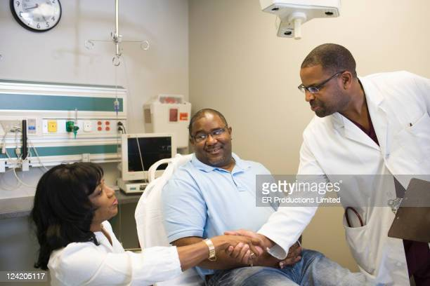 African American doctor shaking hands with patient's wife in hospital