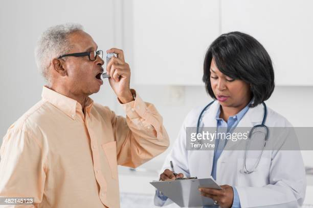 african american doctor with man using asthma inhaler - asthmatic stock photos and pictures